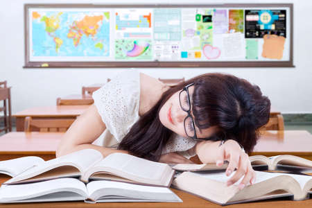 stress test: Female high school student sleeping in the classroom above the books on the table