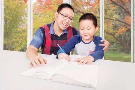 asian boy: Portrait of cute little boy studying with his father near the window at home with autumn background