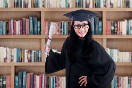 fresh graduate: Excited student wearing graduation gown posing in the library