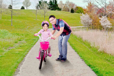 riding helmet: Portrait of cheerful little girl learns riding a bike with her father on the park