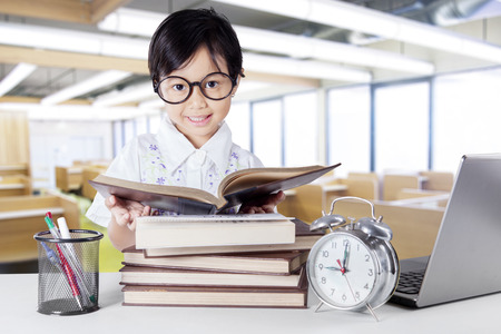 science education: Adorable female kindergarten back to school and reading books in the classroom while wearing glasses