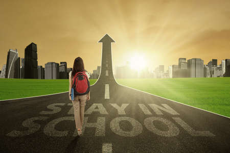 toward: Young student walking on the street turning into arrow upward to stay in school and gain bright future Stock Photo