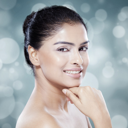Beautiful woman with natural skin smiling at the camera in the studio against bokeh background