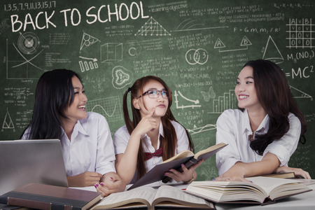 study group: Portrait of three attractive high school students, studying and laughing together in the classroom Stock Photo