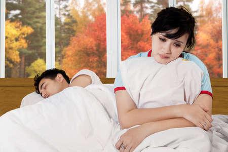arbol de problemas: Retrato de mujer joven infeliz que se sienta en la cama cerca de su marido con el fondo del otoño en la ventana Foto de archivo
