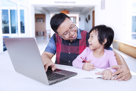father teaching daughter: Female little child talking with her father while doing homework with a book and laptop on the table at home