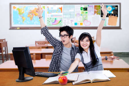 hands high: Portrait of two cheerful high school student studying in the classroom and raise hands together Stock Photo