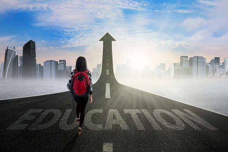 toward: Young student walking on the road with an Education text turning into arrow upward, symbolizing the way to gain higher education