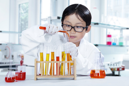 discovery: Portrait of cute little scientist doing research with chemical fluid in the laboratory