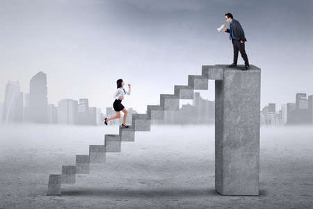run faster: Businessman standing on the bar and calling his colleague to run faster on the stair