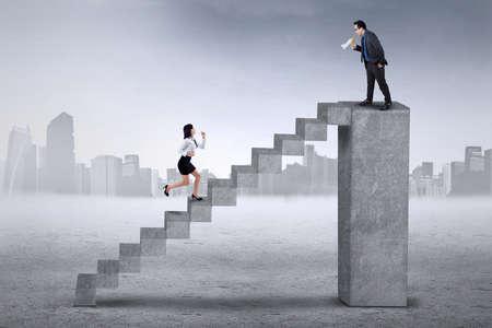 gente corriendo: Empresario de pie en la barra y llamando a su compañero para correr más rápido en la escalera