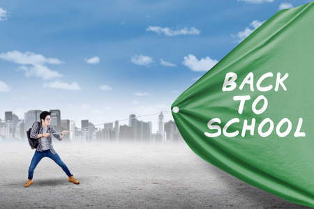 university text: Male college student pulling a flag of back to school, shot outdoors Stock Photo