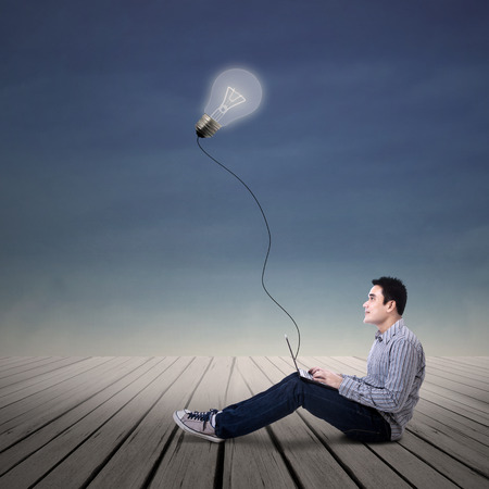 Asian man student looking at lit bulb with laptop outdoor Stock Photo