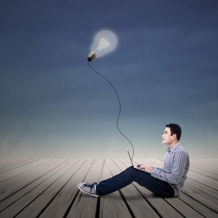 asian man laptop: Asian man student looking at lit bulb with laptop outdoor Stock Photo