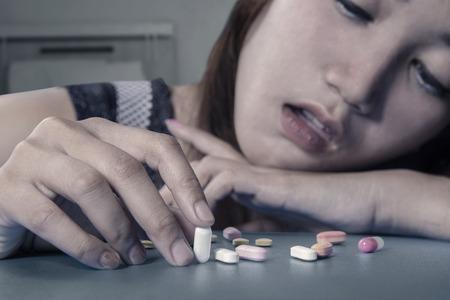 drogadiccion: Deprimido drogadicto femenina celebraci�n de las p�ldoras en la mesa, tiro en el hogar