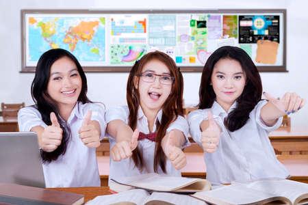 jovenes estudiantes: Retrato de tres atractivas mujeres estudiantes de nuevo a la escuela y que muestra los pulgares para arriba la cámara en el aula