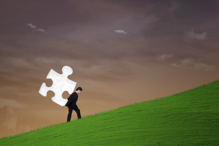asian business: Businessman is carrying a puzzle under sunset sky Stock Photo