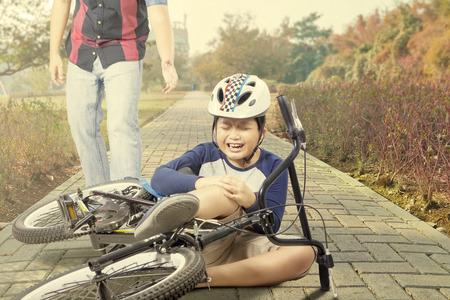 de rodillas: El niño pequeño llevaba casco y llorando mientras sostiene su rodilla después del accidente con su bicicleta