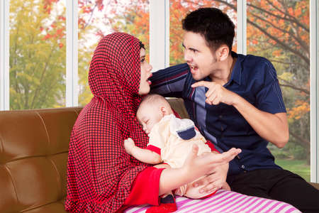 Muslim: Portrait of young man scolding his wife at home while holding a baby, shot with autumn background on the window Stock Photo
