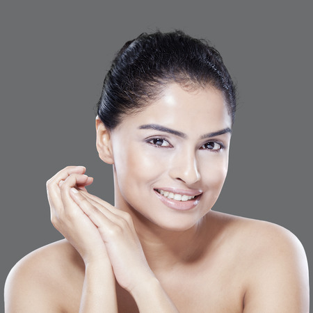 asian natural: Attractive asian female model with nice face and natural skin, smiling at the camera on gray background