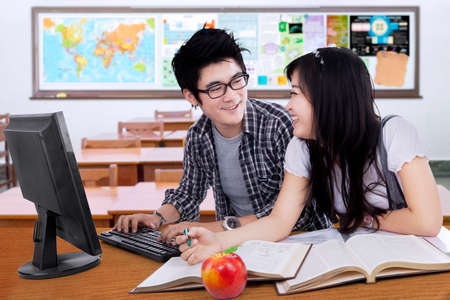 asian youth: Portrait of two college students studying in the classroom while talking and laughing together Stock Photo