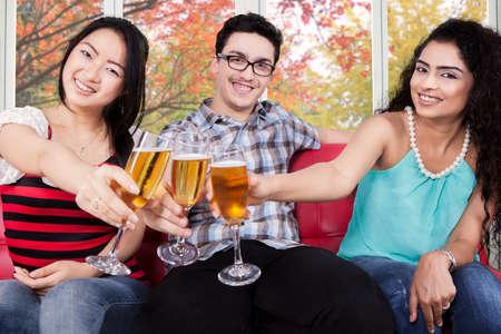 jovenes tomando alcohol: Retrato de tres multi pueblo étnico potable y tostado champán con fondo de otoño