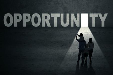 opening door: Portrait of family walking toward an opportunity door