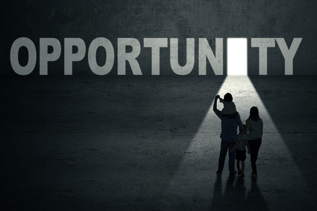 opportunity concept: Portrait of family walking toward an opportunity door