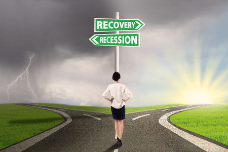 road to recovery: Female worker standing on the road and look at the signpost pointing on the road to recovery or recession finance