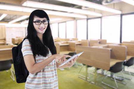 Smiling female student using a tablet computer in a library