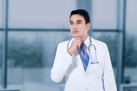 serious doctor: Portrait of young handsome doctor thinking about something with hand on chin Stock Photo