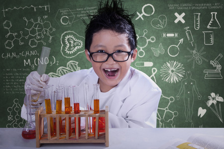 scientist: Mad little scientist doing experiment with chemical fluid and looking at camera