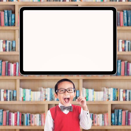 nios en la escuela: Joyful masculina que se�ala estudiante de la escuela primaria a una pizarra en blanco en la biblioteca Foto de archivo