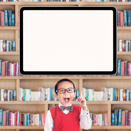 primární: Radostné samec základní školy student ukázal na prázdnou tabuli v knihovně Reklamní fotografie