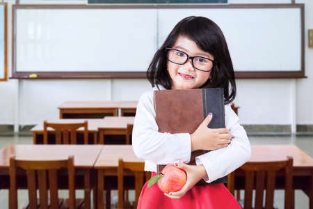 school book: Portrait of little girl back to school and standing in the classroom while wearing glasses and holding a book with apple