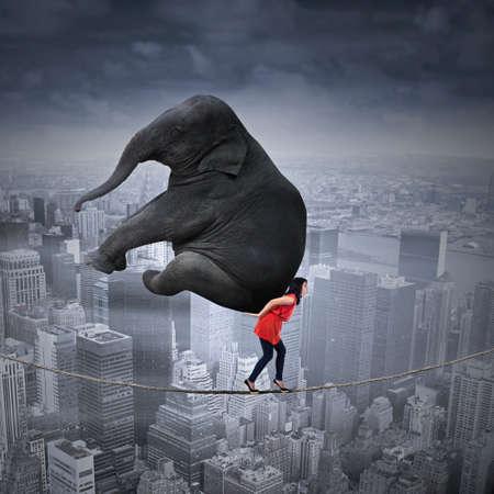 carga: Retrato de mujer que llevaba elefante pesado mientras camina en la cuerda sobre una gran ciudad