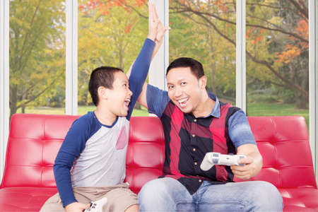 playstation: Portrait of young father playing playstation with his son and claps hands to celebrate the winning Stock Photo