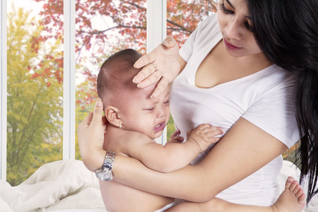sick baby: Young mother checks the temperature of a sick baby at home Stock Photo
