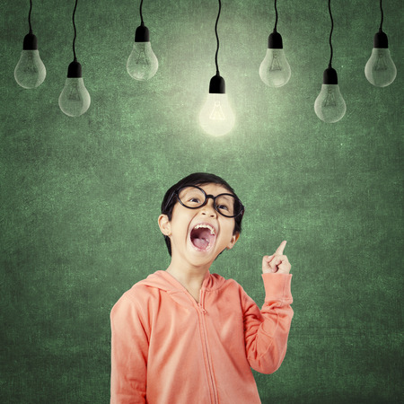 Portrait of cheerful little girl standing in the class under a bright light bulb Stock Photo