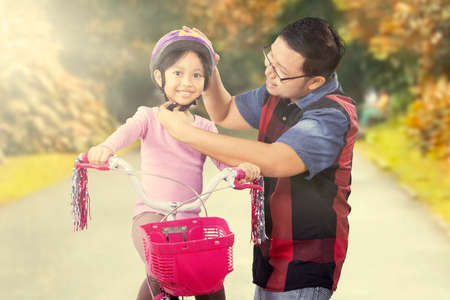 fall protection: Young man fasten helmet on the daughter head while riding a bike on the park Stock Photo