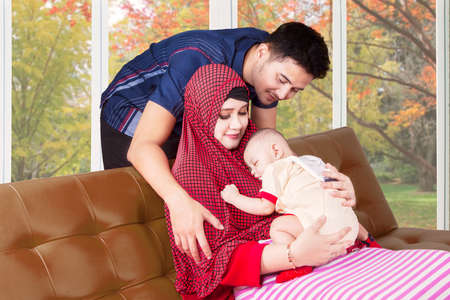 muslim baby: Portrait of two muslim parents and their baby sleeping on the mothers chest, shot on the sofa at home Stock Photo