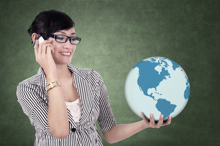 business globe: Asian businesswoman with globe on chalkboard