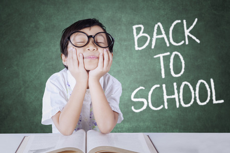 daydream: Portrait of little girl back to school and daydream in the classroom while wearing glasses with book on the table
