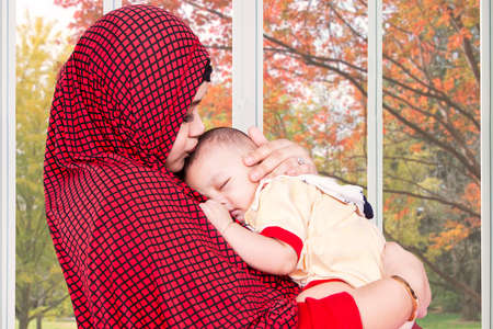 beautiful mother: Portrait of muslim mother wearing veil and lull her baby near the window at home