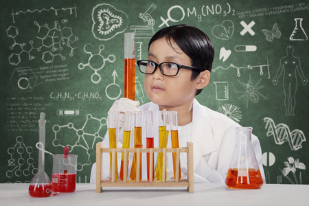 experimento: Retrato del estudiante masculino abrigo que llevaba y hacer experimento de química en el laboratorio con el fondo garabatos en la pizarra