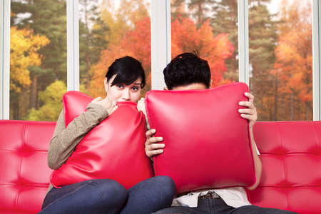 horror movie: Scared couple covering their face while watching horror movie at home Stock Photo