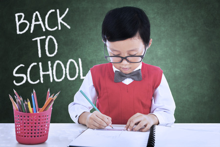 kid book: Male elementary school student back to school and drawing in the classroom while wearing uniform Stock Photo