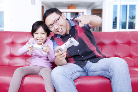 playstation: Attractive little girl playing playstation with her father while sitting on the sofa at home