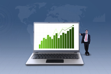 asian man laptop: Businessman standing next to laptop with increasing bar chart on blue world map background Stock Photo