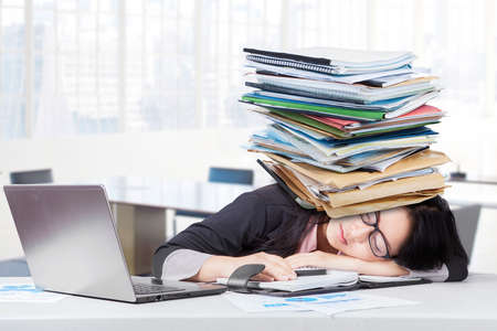 paperwork: Frustrated businesswoman sleeping in the office with paperwork on head and laptop on the table